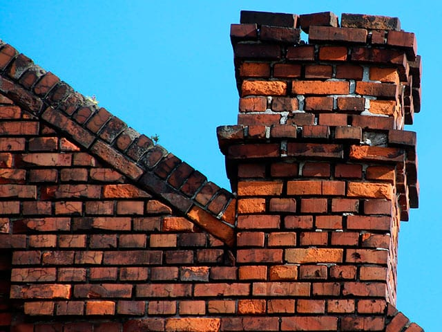 leaning and crumbling brick chimney