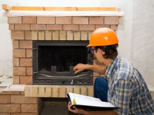 man inspecting fireplace
