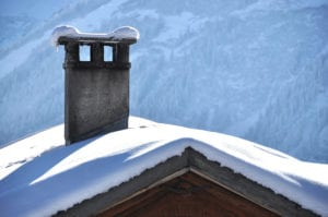 snowy chimney and roof with mountains in background